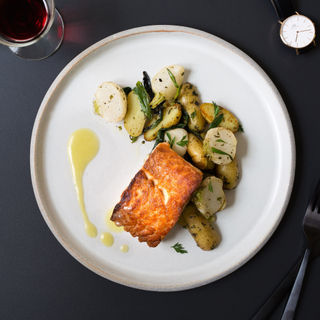 salmon fillet with ginger-miso sauce, roasted potatoes and turnips on a white dinner plate