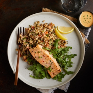 white plate with roasted salmon fillet, quinoa tabbouleh and fresh arugula with lemon slices
