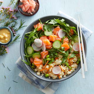 Blue bowl of salmon poke rice bowl with white chopsticks, chopped fresh salmon, radishes and greens on a light blue background with a folded napkin.