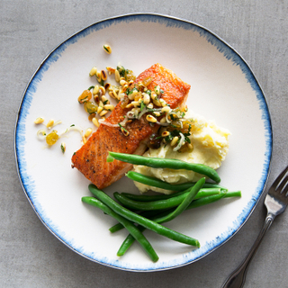 White dinner plate with blue edges holding green beans, roasted salmon, mashed potatoes and caper relish on top with a fork on the side on a grey background.