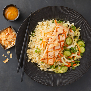 Salmon fillet over broken rice salad with cucumbers and shaved vegetables on a black round dinner plate with black chopsticks.