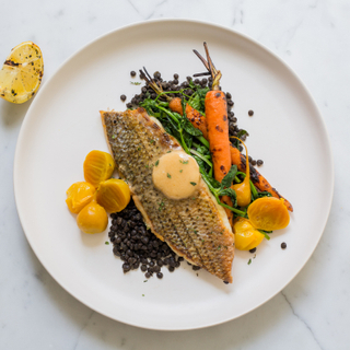 Seared sea bass fillet on a bed of black lentils with cooked whole carrots and golden beets on a white round dinner plate.