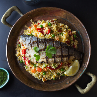 Copper pot filled with paella rice with a half branzino sea bass grilled and topped with fresh herbs. Served with a lime wedge and a dish of chimichurri sauce on the side.
