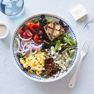 cobb salad with grilled salmon, onions, tomatoes, corn and lettuce in a bowl