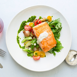 seared salmon fillet with mustard dressing, green and fresh raw vegetable salad on a white dinner plate