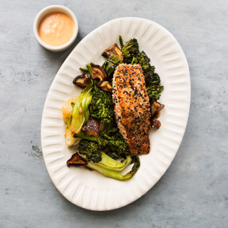 Large white platter with sesame seared salmon, sauteed greens and a side of dipping sauce on a grey concrete background