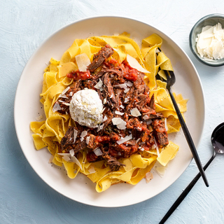 pappardelle pasta with braised short rib sauce and grated cheese on a white dinner plate