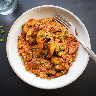 shrimp and andouille sausage jambalaya with rice and scallions in a white bowl