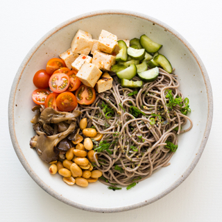 Soba noodle and grilled tofu salad with sliced cucumbers, cherry tomatoes, peanuts and mushrooms in a white bowl on a white table with wooden chopsticks