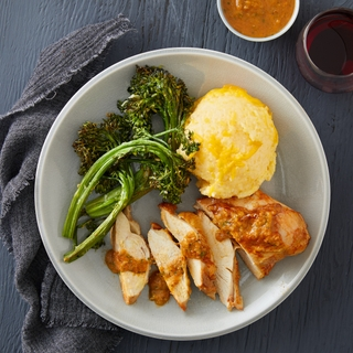 sliced southwestern spiced chicken breast with cheesy polenta and roasted broccolini in a white bowl
