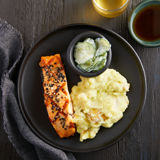 Black dish with one fillet of soy-glazed salmon next to wasabi mashed potatoes and a small black dish of cucumber salad with sour cream.