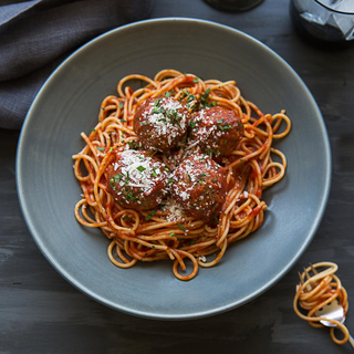 grey bowl with spaghetti and four large meatballs topped with grated cheese and minced herbs