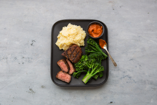 Spanish-style grilled tri-tip steak, roasted broccoli, mashed potatoes and romesco sauce on a black dinner plate