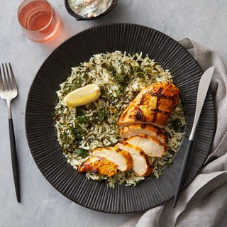 Spanakopita rice with spiced grilled chicken sliced into thin slices on a black round plate with a slice of fresh lemon on top with a fork and a knife on the side.