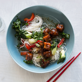 blue bowl with sticky black pepper tofu, rice noodles, red peppers and greens next to red chopsticks
