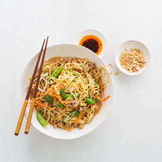 dan dan noodles with fresh vegetables and sauce in a white bowl and chopsticks