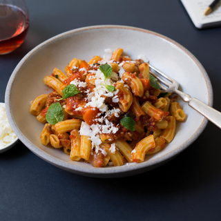rigatoni pasta with spicy pork ragu and grated cheese in a white pasta bowl