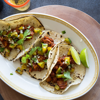 three spicy pork tacos on an oblong white plate with fresh lime, pineapple and cilantro