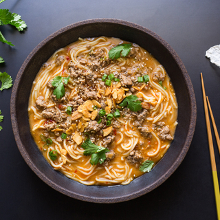 spicy tan tan pork ramen in a black bowl with ground pork, noodles and fresh herbs