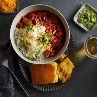 Spicy turkey chili topped with shaved cheese in a white bowl on a dark plate with a side of cornbread on a dark background with a glass of wine on the side and a fork in the corner.