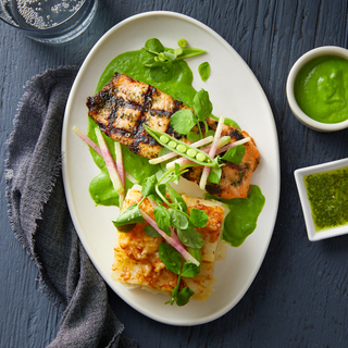 Spring salmon fillets with a square slice of potato gratin and bright green sauce on a white plate with raw vegetables for garnish on a dark wood background.