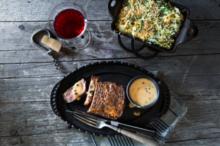Steak au poivre on a black oblong plate with sauce in a dish on the side and spinach gratin with a glass of red wine in the corner on a wooden table.