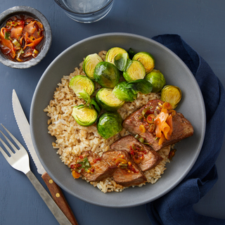 steak brown rice bowl with steamed brussels sprouts and ginger-soy dressing