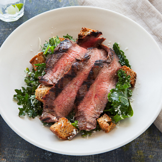 Salad with large slices of rare steak, kale and croutons on a white bowl with a white linen napkin in the background.