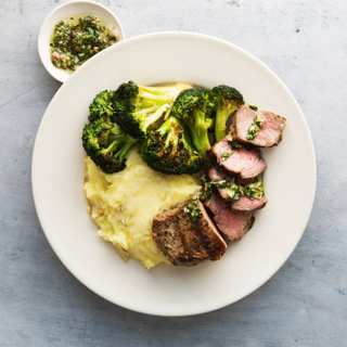 Sliced grilled steak on parmesan mashed potatoes with roasted broccoli on a white plate.