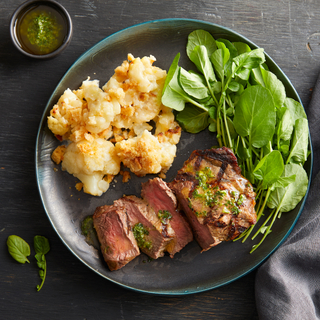 grilled sliced steak with cauliflower gratin and fresh lettuce on a black dinner plate