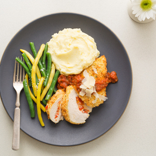 stuffed chicken parmesan with mashed potatoes and green and yellow beans on a black dinner plate
