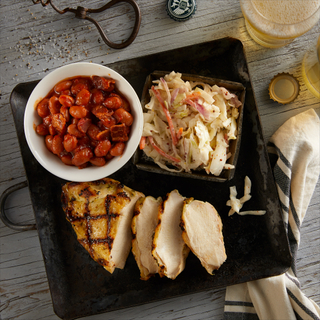 Summer BBQ chicken plate with grilled chicken sliced into three pieces on a black square plate with a bowl of bacon ranchero beans and a plate of coleslaw on a wooden table with a glass of beer.
