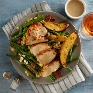 sliced chicken breast over a salad of green beans, corn and roasted fingerling potatoes on a grey dinner plate with a grey and white striped dish towel