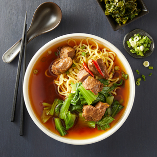 Taiwanese beef noodle soup with noodles, chunks of beef, chopped greens in a white bowl with a black spoon and black chopsticks on the side.