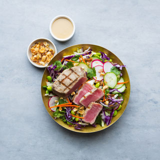 grilled ahi tuna steak sliced over a salad of colorful mixed raw vegetables