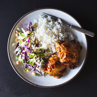 teriyaki chicken thighs with white rice and asian cabbage slaw on a white plate