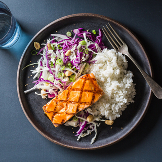 teriyaki glazed salmon fillet on steamed white rice with purple cabbage slaw