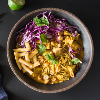Thai chicken curry noodles with red cabbage, fresh cilantro in a black round bowl on a black background with a blue napkin and black chopsticks.