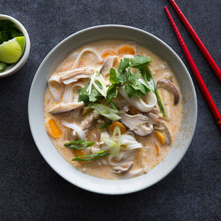 bowl of thai chicken curry soup with rice noodles, fresh herbs and colorful vegetables