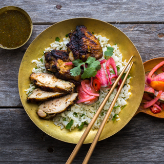 Thai grilled chicken on cilantro rice with pickled red onions on a gold round plate with brown chopsticks on a wooden table with a side of pickled vegetables in a small plate.