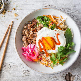 thai pork bowl with a fried egg, ground pork and brown rice in a white bowl with chopsticks