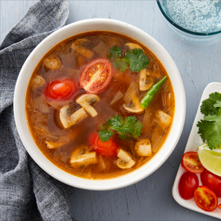 Tom yum soup with sliced tomatoes and mushrooms and fresh cilantro in a white bowl next to a white plate of sliced vegetables and lime on a blue background with a glass of water.