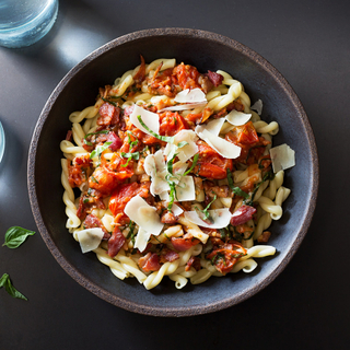 black bowl of tomato, bacon and gemelli pasta with shaved cheese