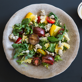Tomato sweet corn salad with arugula, sliced tomatoes and cheese on a stone plate on a dark blue background with dressing on the side.