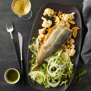 grilled trout with brown butter cauliflower and green salad on a black long plate with a glass of wine