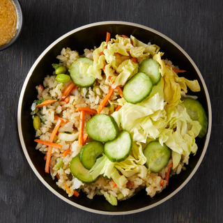Vegan gaba rice bowl with rice, sliced cucumbers, green cabbage and carrots in a black bowl with a black background.