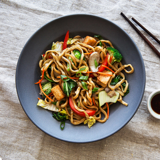 black bowl with vegetable and tofu lo mein with wooden chopsticks and a dish of soy sauce