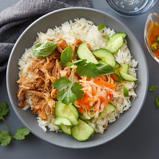 Vietnamese pork belly bowl with sushi rice, sliced cucumbers and carrots with shredded pork in a blue bowl on a dark background.