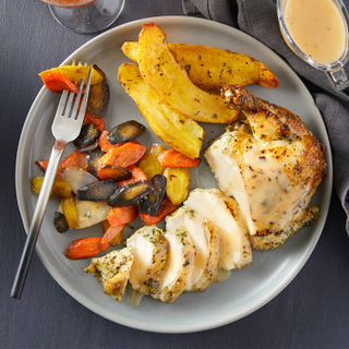 Weeknight roast chicken dinner sliced into pieces next to crisp potatoes and roasted carrots on a blue plate with a grey napkin and gravy on the side.