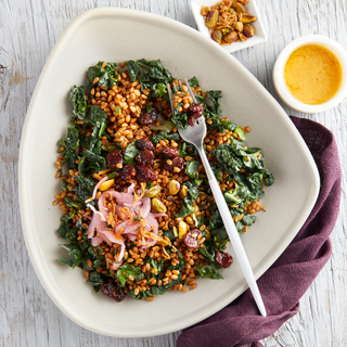 Wheat berry salad with cooked greens and pickled onions on a white bowl on a white wooden table with a purple napkin.